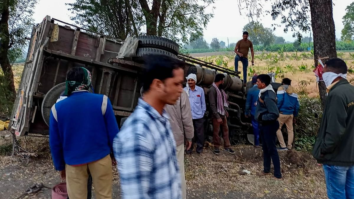 People gather near the mangled remains of a truck after it overturned near Kingaon village, killing at least 16 labourers, in Jalgaon district of Maharashtra, Monday, 15 February.