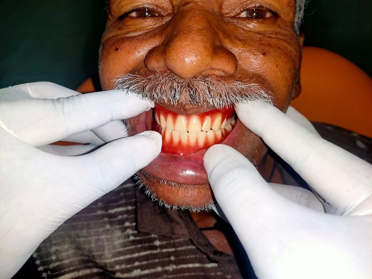 Baskaran showing off his new set of teeth.