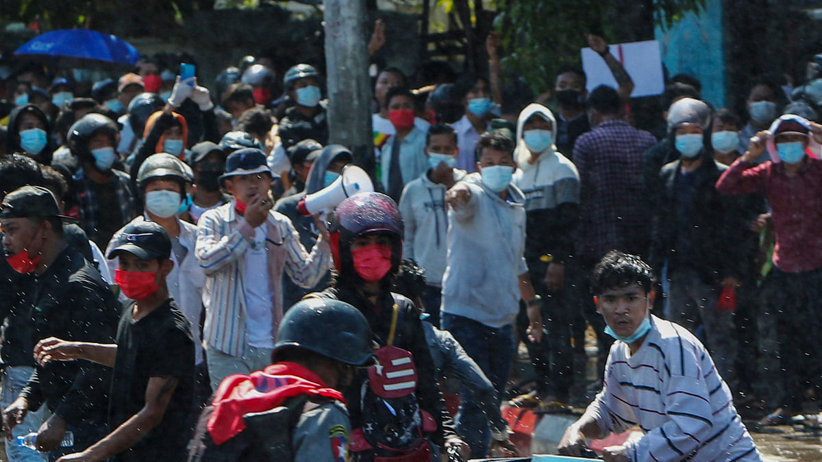 File photo of protesters running after police fired warning shots and water cannon to disperse them during a protest in Mandalay, Myanmar, in February.