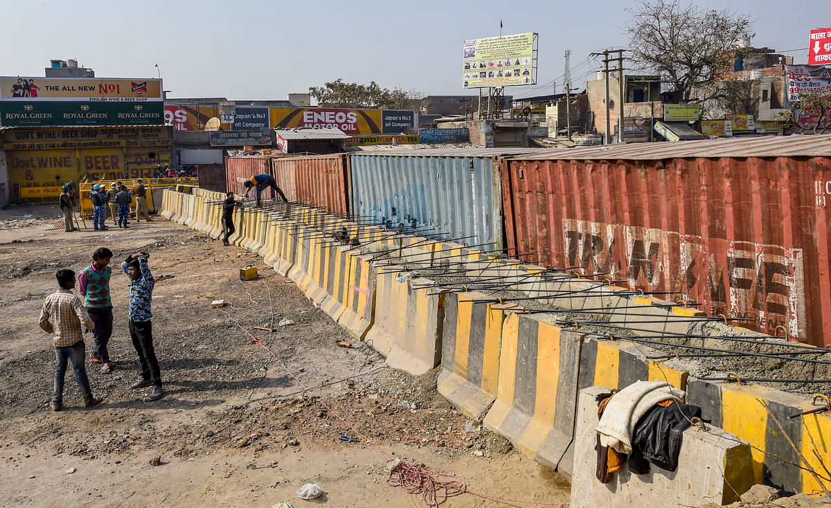 Barricades being set up as part of security enhancements by the police near the site of farmers ongoing protest against farm reform laws, at Singhu Border in New Delhi on Monday.