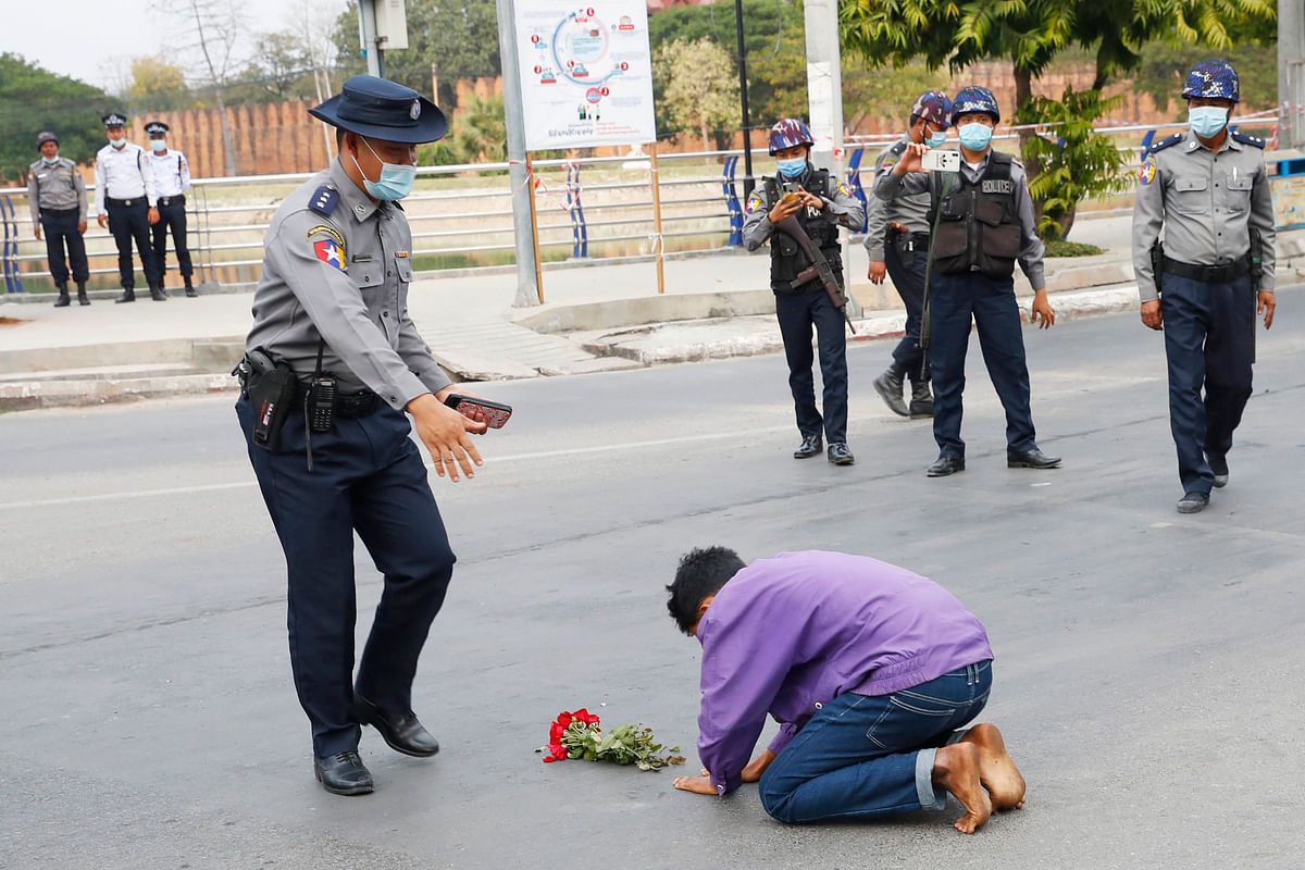 A protest supporter offers flowers and kneels on a road before a police officer in Mandalay, Myanmar, on Feb. 6, 2021
