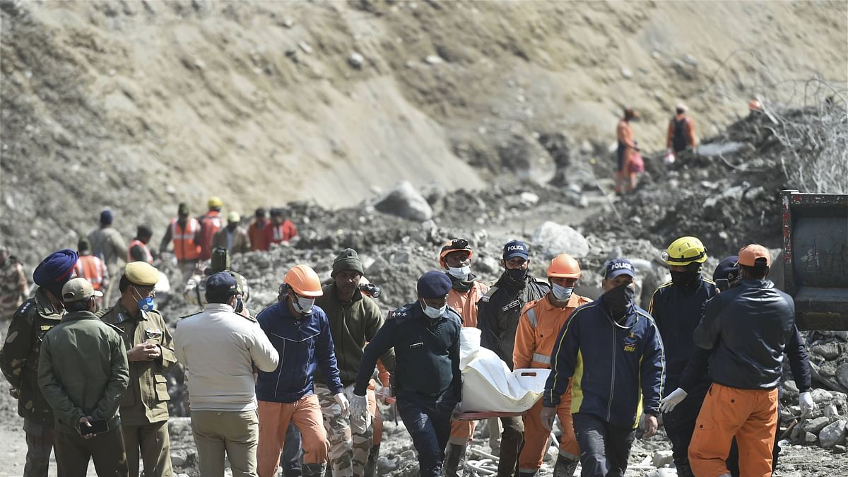 NDRF personnel carry the mortal remains of a flash flood victim near Raini village.