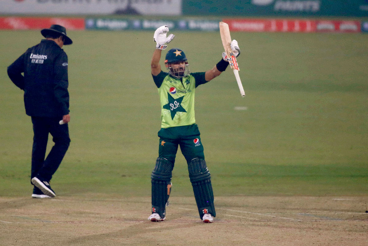 Pakistan's Mohammad Rizwan, center, raise bat to celebrate his fifty during the 2nd Twenty20 cricket match between Pakistan and South Africa at the Gaddafi Stadium.