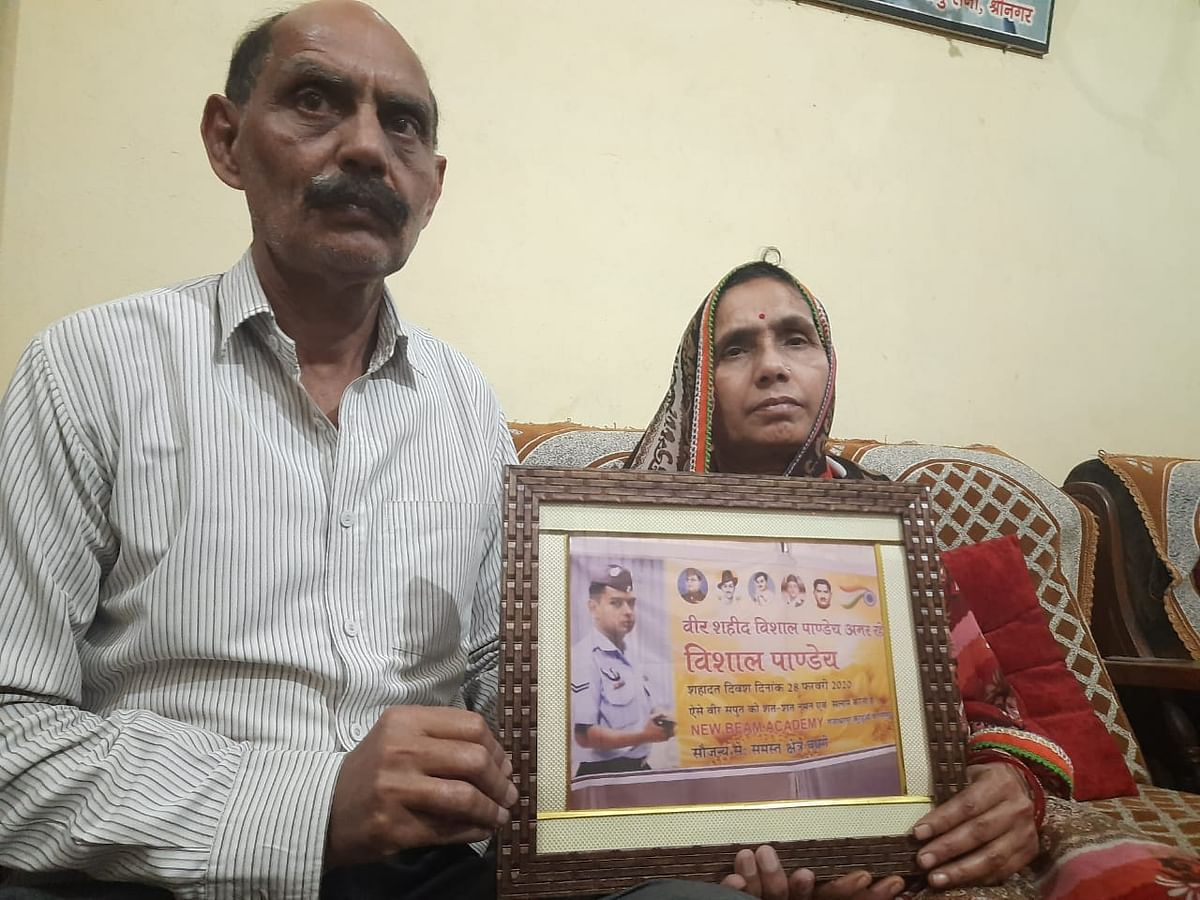 <p>Vijay Shankar Pandey and his wife holding a photograph of their martyred son, Vishal Pandey.</p>