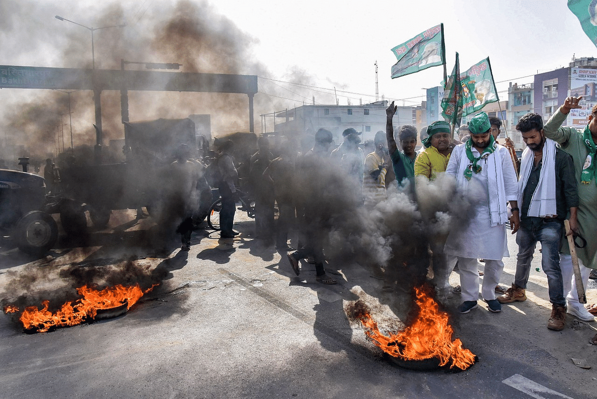 Activists burn tyres as they block a road during a nationwide strike, called by farmers unions against the three farm laws, in Patna, Friday, March 26, 2021.