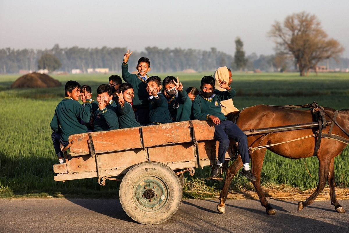 Students travel towards their school on a horse-cart, after schools re-opened since its closure on March 2020 due to the coronavirus pandemic, on the outskirts of Jammu, Wednesday, 3 March, 2021.
