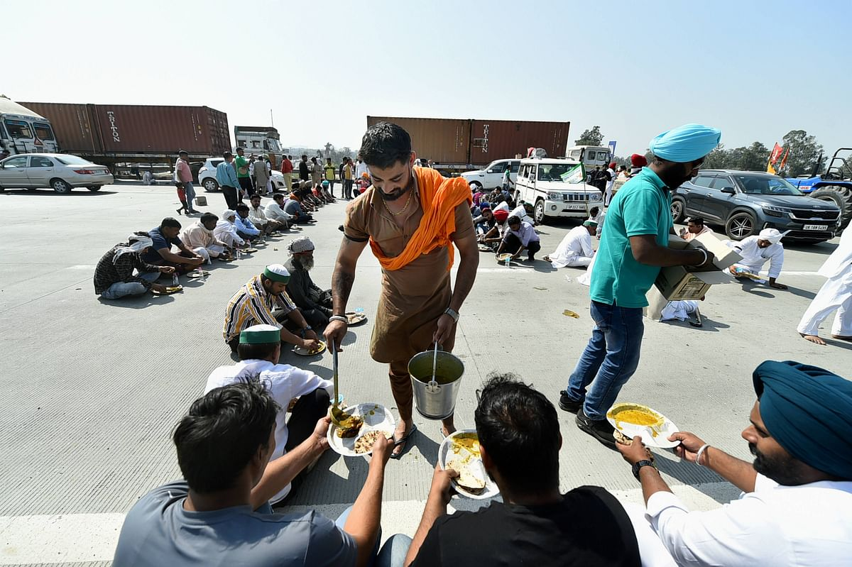 Farmers having their meal as they block the KMP Expressway near Duhai to mark the 100th day of their ongoing agitation against Centres farm reform laws, in Ghaziabad.