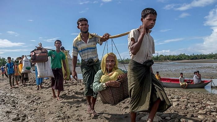 Rohingya Muslims, who crossed over from Myanmar into Bangladesh, carry an elderly woman in a basket and walk towards a refugee camp in Shah Porir Dwip, Bangladesh, 14 September 2017.