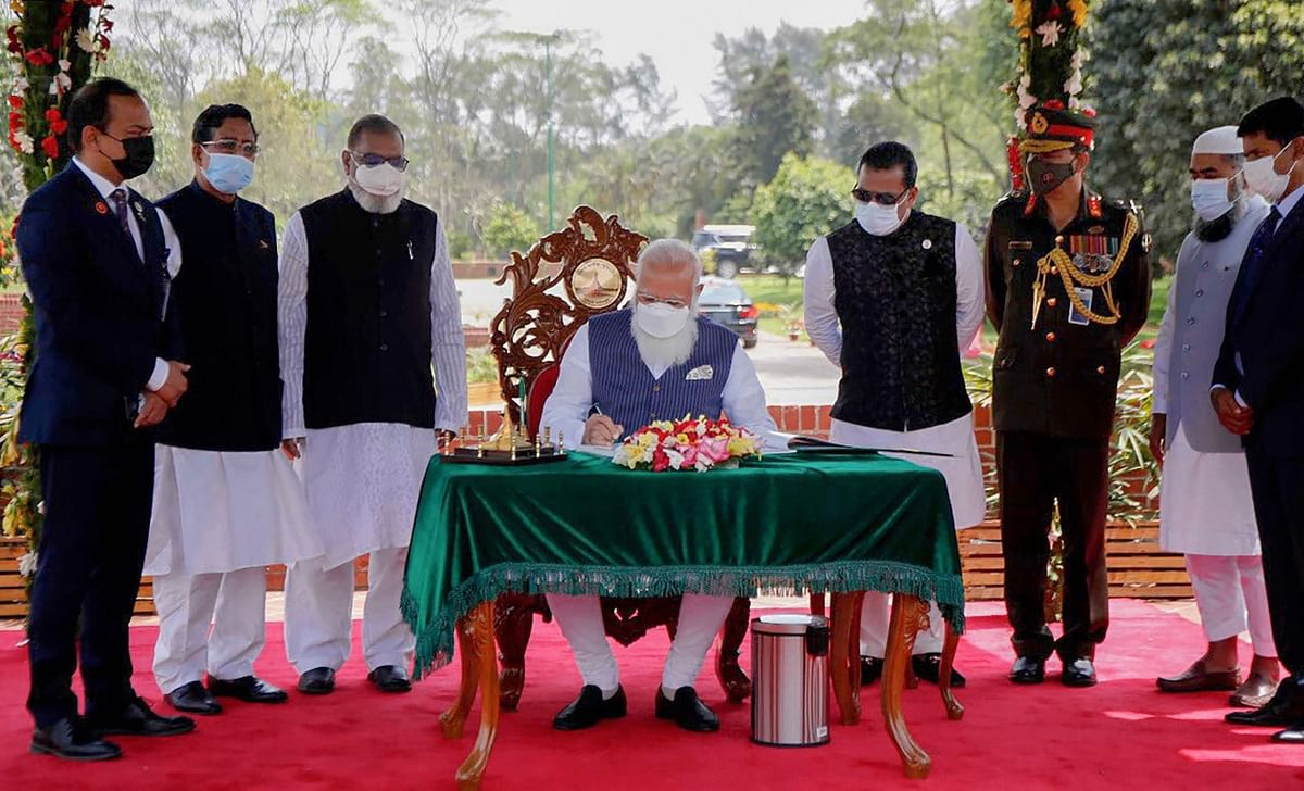Prime Minister Narendra Modi signs the visitor book at the National Martyr's Memorial in Savar, on the occasion of 50th Independence Day of Bangladesh, in Dhaka, Friday, March 26, 2021