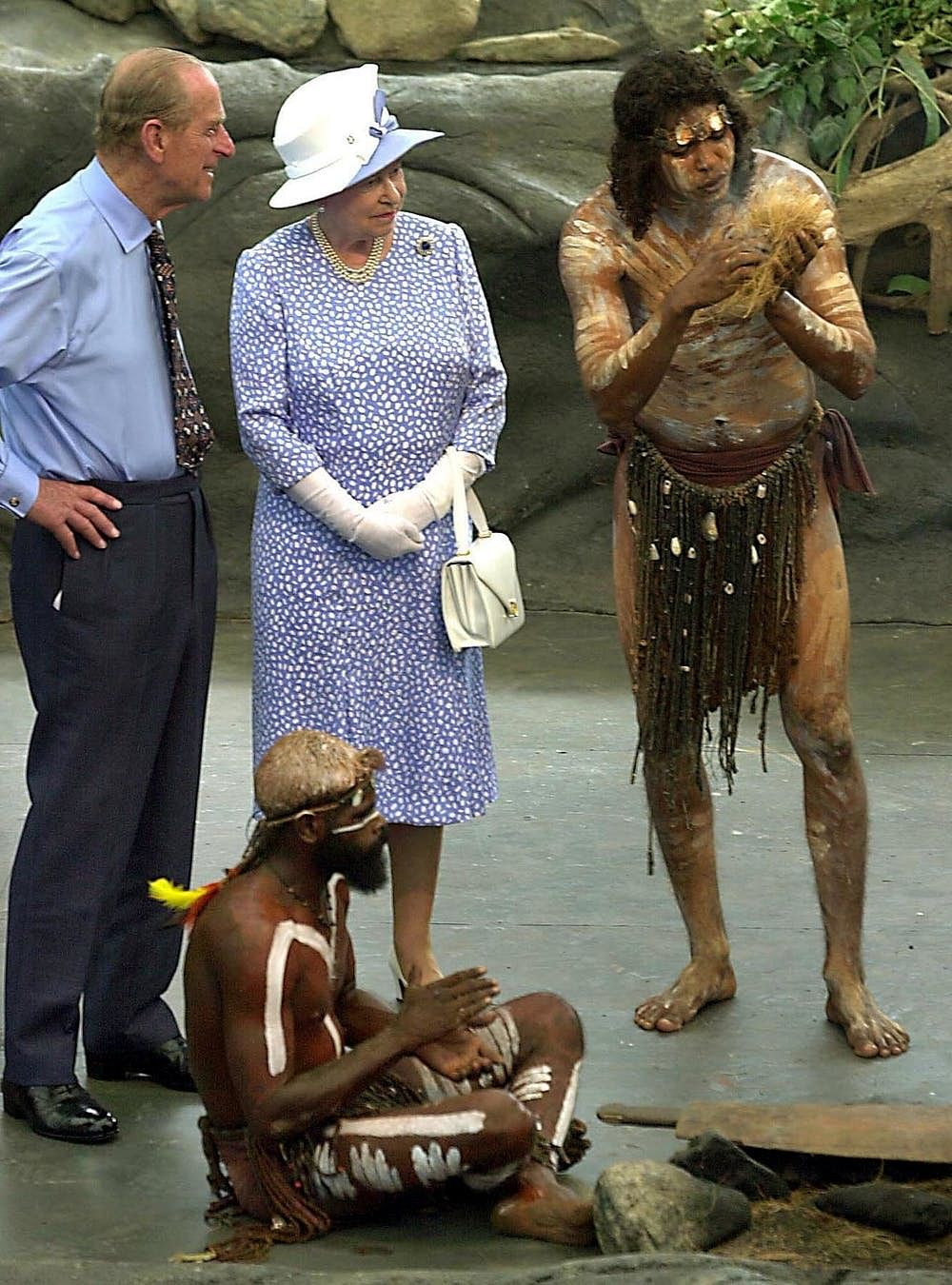Queen Elizabeth II and Prince Philip watch as Warren Clements of the Tjapakai Aboriginal Dance Group makes fire by rubbing sticks in Cairns in March 2002.