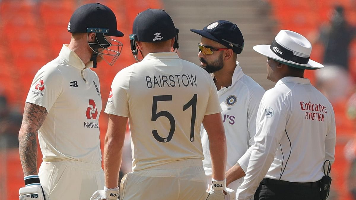 Ben Stokes, Jonny Bairstow and Virat Kohli have a conversation mid-pitch.
