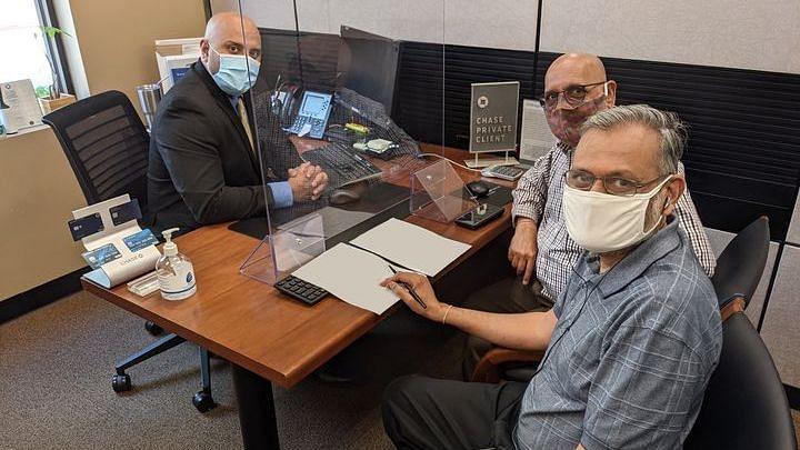 Arun Kankani, President of Sewa International USA, and Yagnesh Patel, Compliance Manager of Sewa International USA, at the bank.