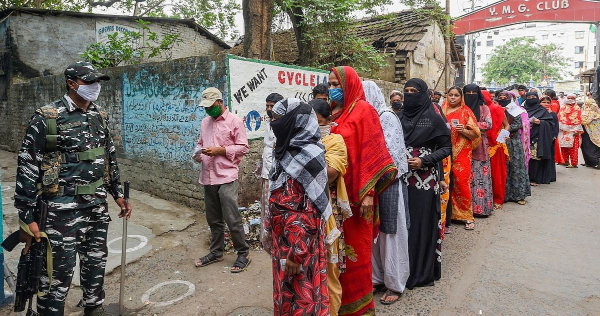 People stand in a queue to cast their vote at a polling station during the 6th phase of State Assembly Election at Birati, in North 24 Parganas.