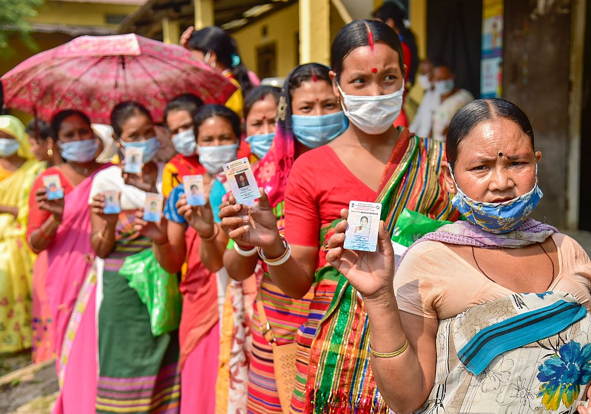 Kamrup: Hajong tribal women show their voter identity cards as they wait in the queue to cast their votes at a polling Station for Assembly polls, at Boko in Kamrup district, Tuesday, April 6, 2021.
