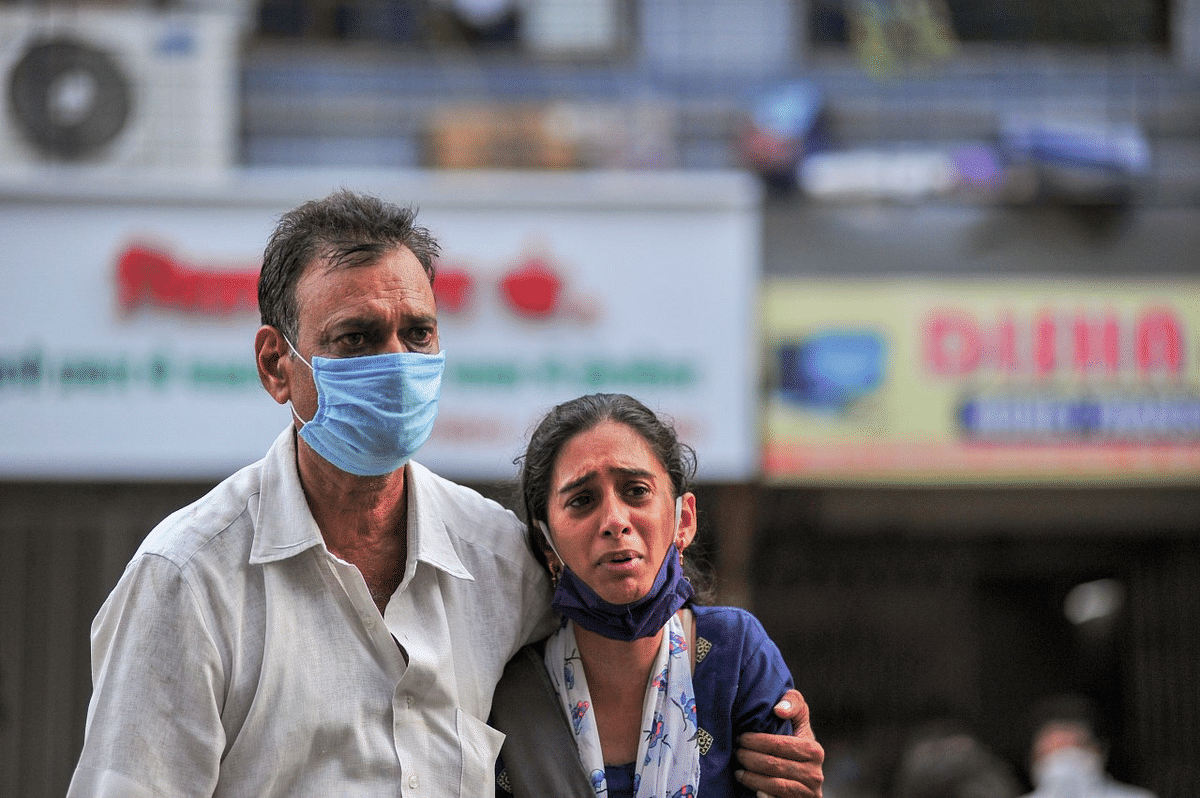 Family members react after a fire at a Covid-19 hospital where at least 13 people died, in Virar