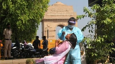 Health worker wearing PPE kit collects swab sample for COVID-19 testing at India Gate in New Delhi.