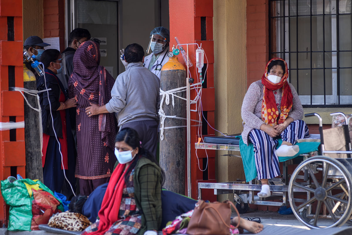 A COVID-19 patient receives oxygen outside an emergency ward as they wait for a bed to be allotted at Tribhuwan University Teaching Hospital  in Kathmandu, Nepal on Friday, May 7, 2021.