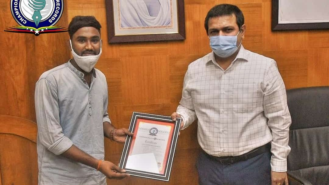 """<div class=""""paragraphs""""><p>Kaki Santosh receiving an award for her service from the district collector.</p></div>"""