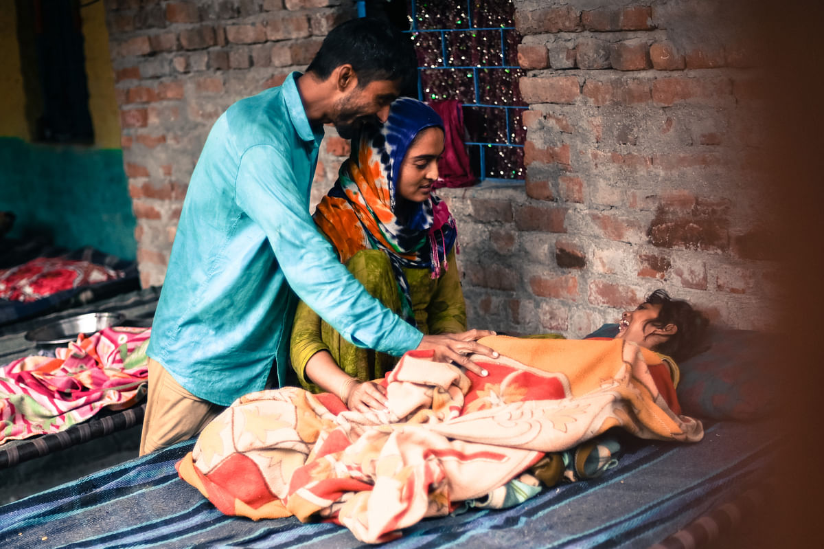Naseeba and her husband Mussadi play with their daughter in the refugee settlement in Majnu ka Tila, New Delhi.