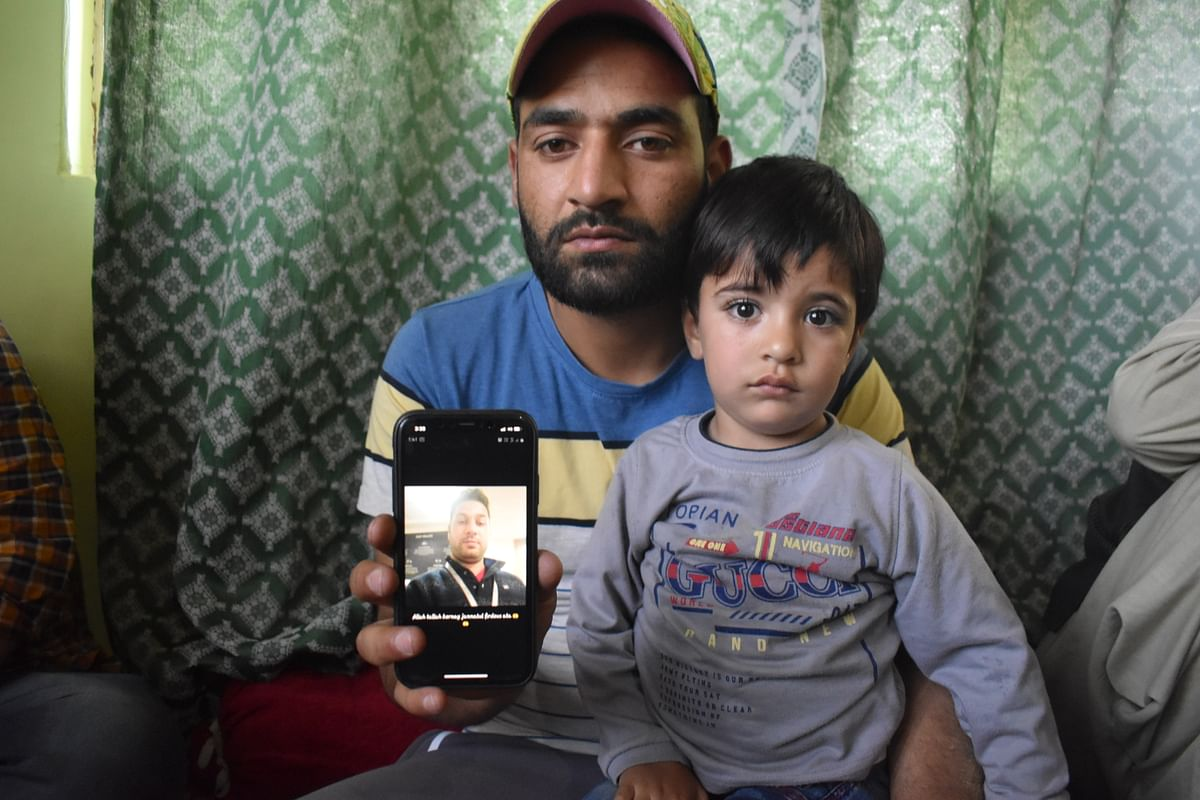 Firdous Ahmad, brother of slain civilian (Manzoor Ahmad, who was killed in Sopore attack) on Saturday, along with the son of Manzoor Ahmad, showing the photograph of his brother (Manzoor Ahmad).