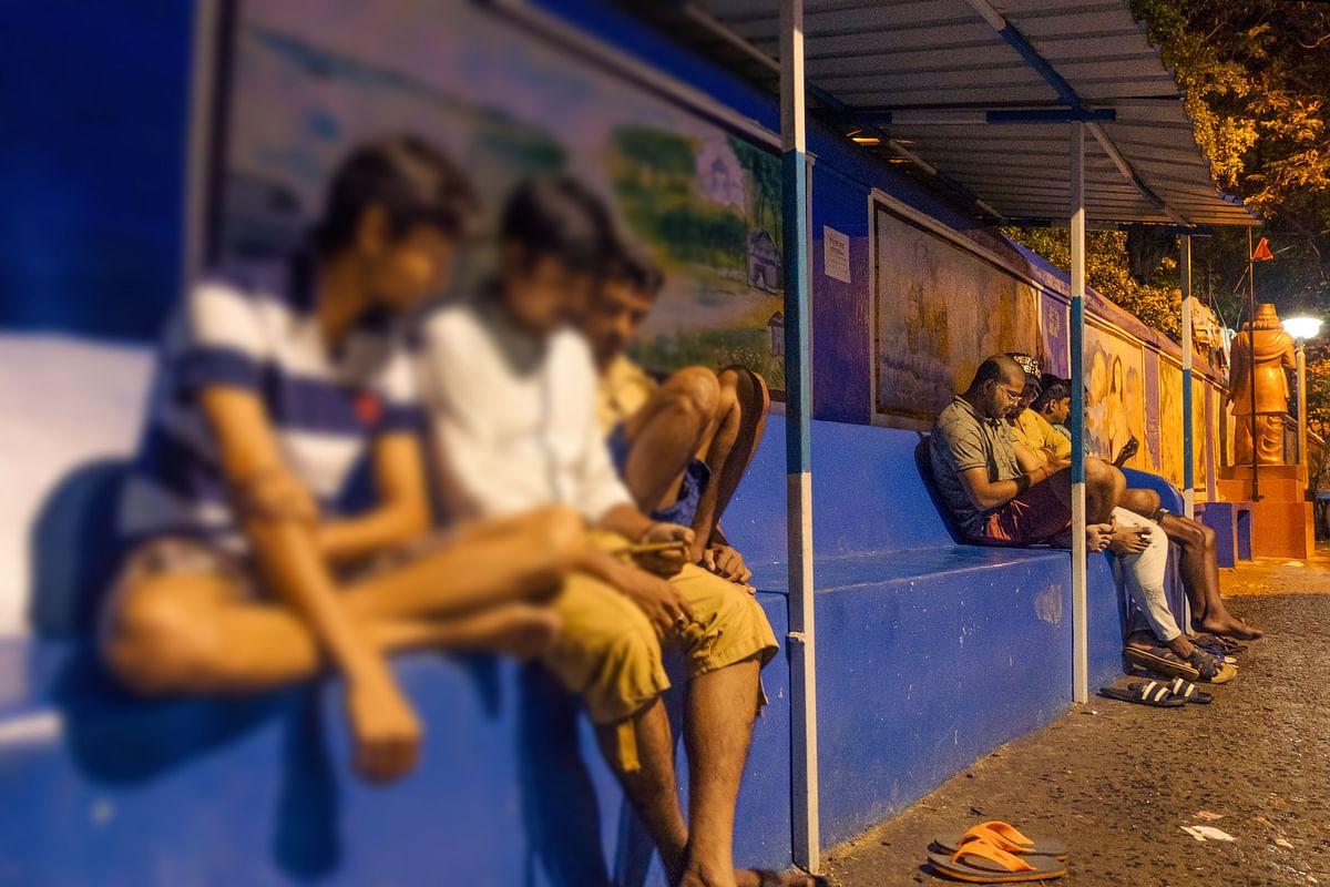Locals sit outdoors in Alambajar, Kolkata.