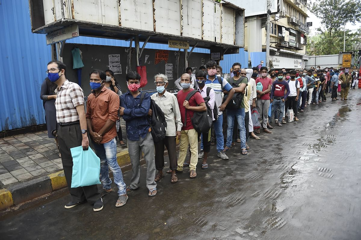 People wait in a queue for a bus after unlocking of COVID-19 lockdown began in a phased manner, at Bandra in Mumbai.