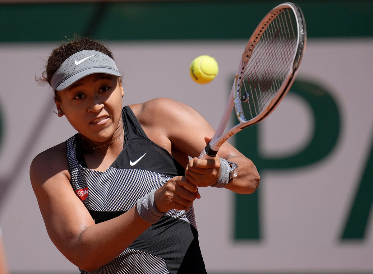 """<div class=""""paragraphs""""><p>Paris: Japan's Naomi Osaka returns the ball to Romania's Patricia Maria Tig during their first round match of the French open tennis tournament at the Roland Garros stadium Sunday, May 30, 2021.</p></div>"""