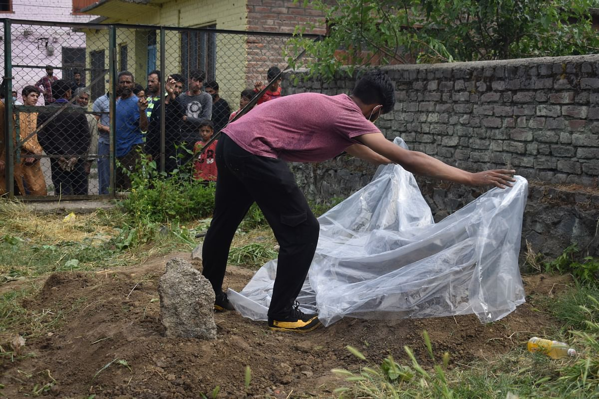 Junaid Bashir, son of slain civilian (Bashir Ahmad) killed in Sopore attack, wrapping polythene on fathers grave to protect it from rain.