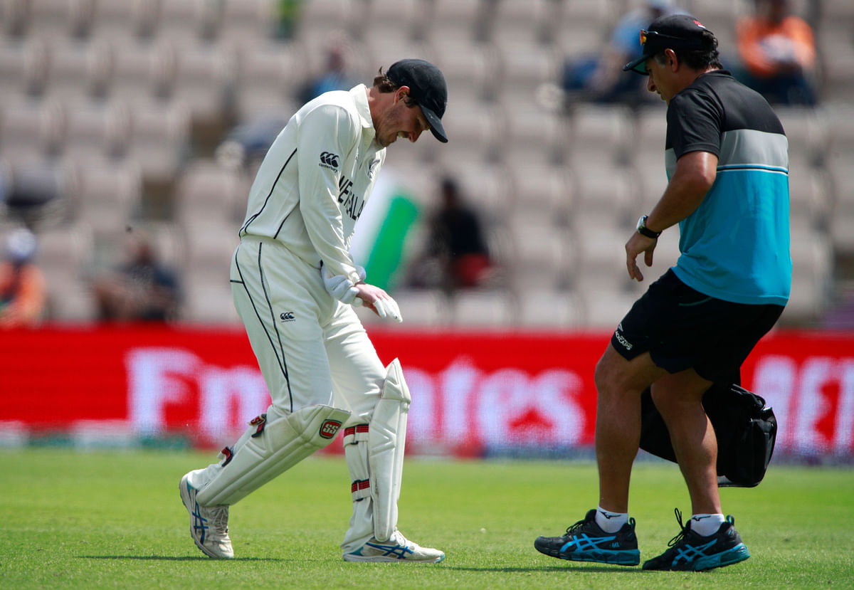 New Zealand wicketkeeper BJ Watling, left, reacts in pain after getting hurt in an attempt to catch the ball during the sixth day of the World Test Championship final cricket match between New Zealand and India.