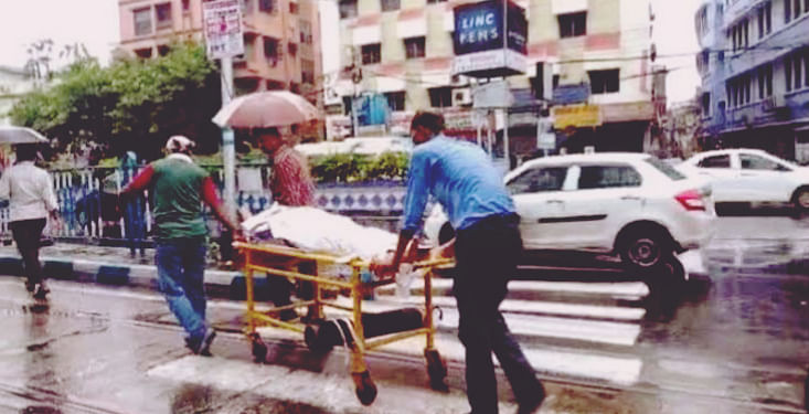 Patient shifted on stretcher amid heavy rains in Kolkata.