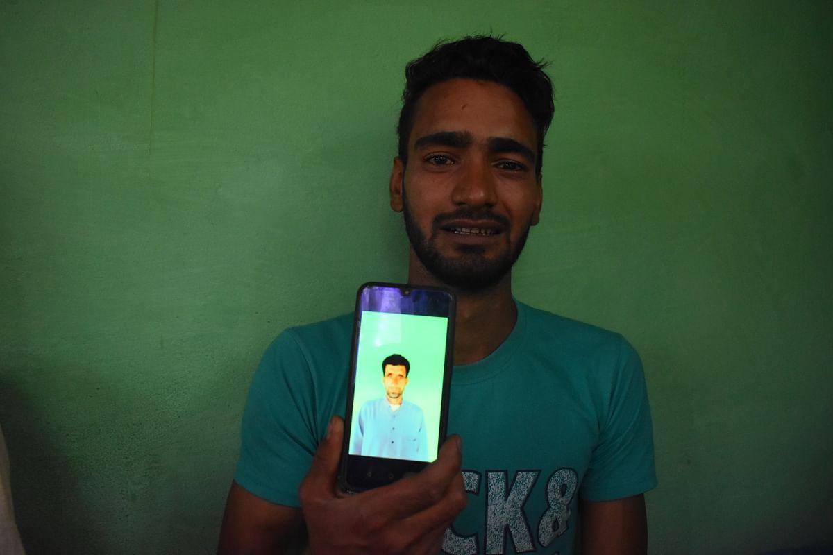 Junaid Bashir, Son of slain civilian (Bashir Ahmad) showing the photo of his father killed in Sopore attack on Saturday.