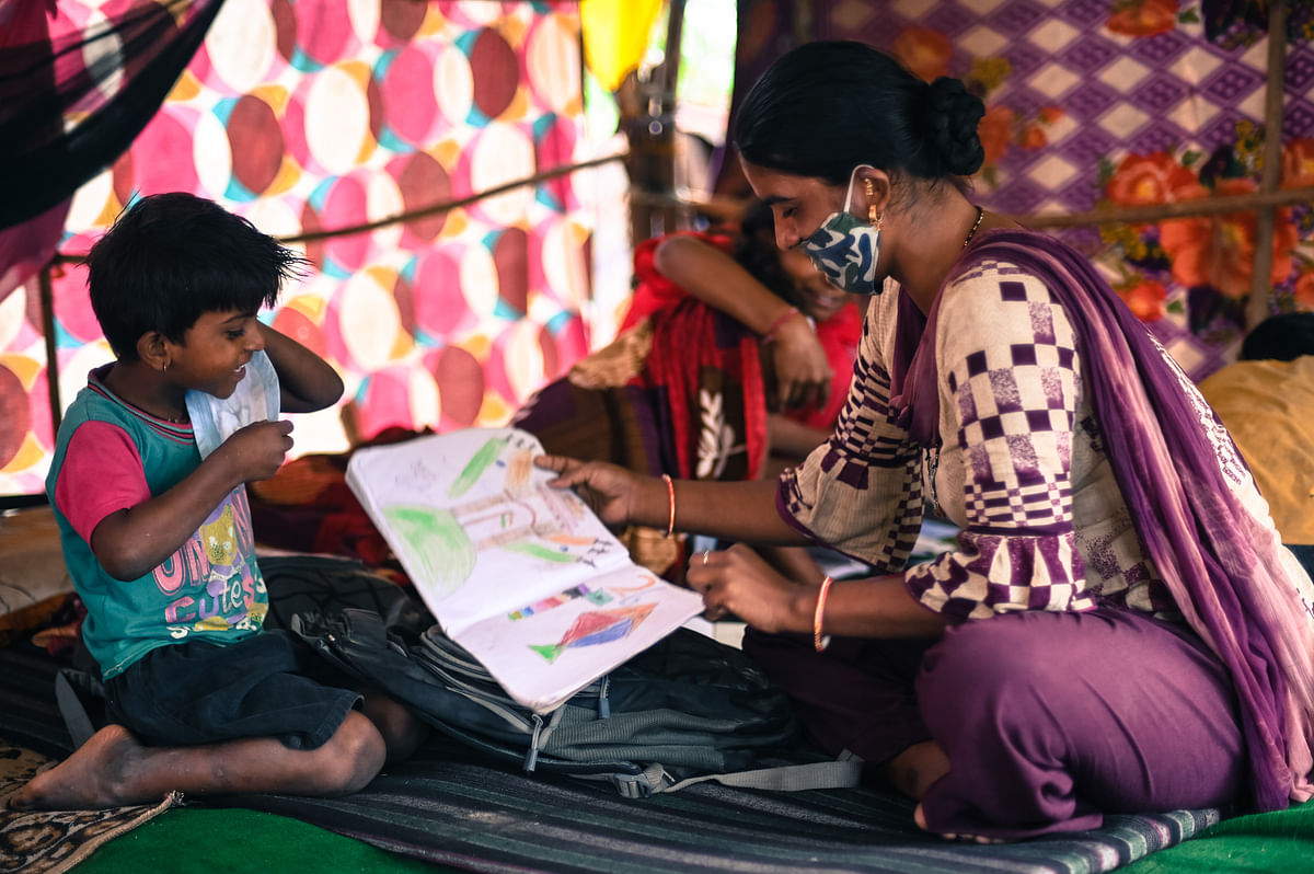 Reshma, 30, plays with her children at the Signature bridge refugee camp in New Delhi. The mother of four children has been concerned about how the lockdowns have affected their education.