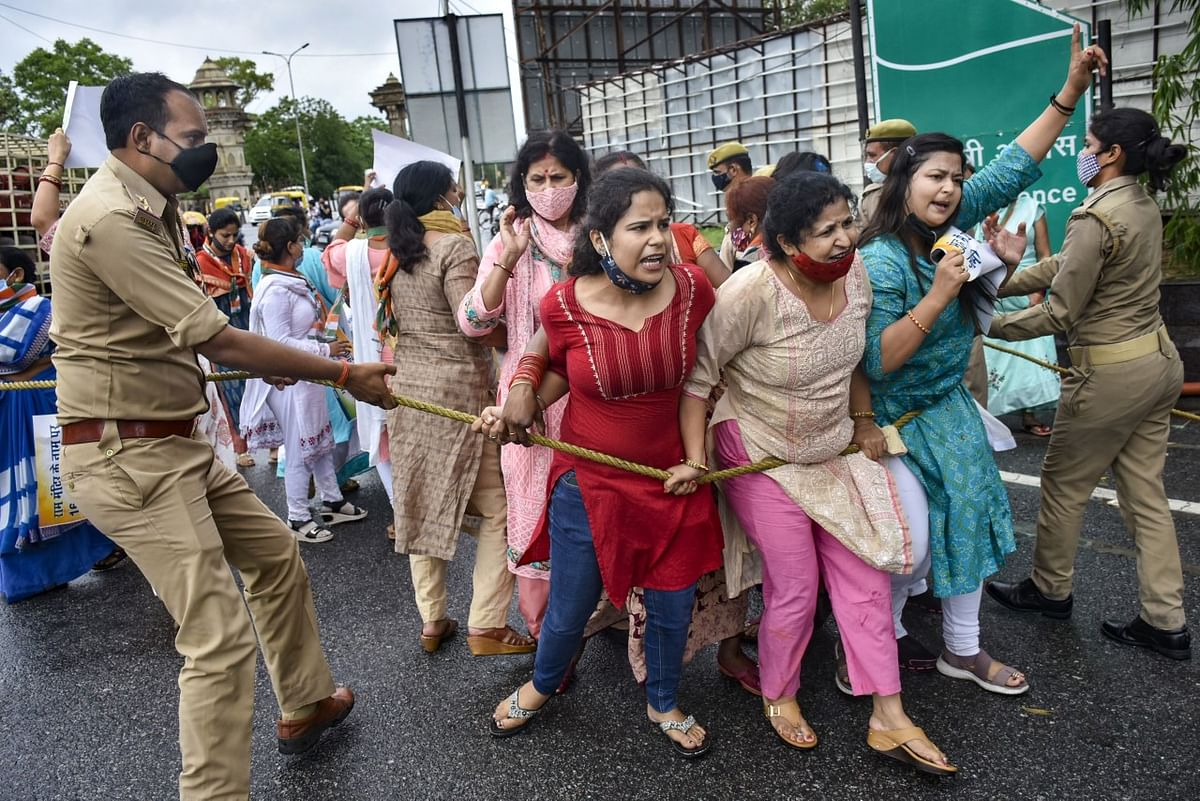 Police personnel try to stop Congress workers protesting against the alleged Ram Mandir Trust land scam, near the CM's residence in Lucknow.