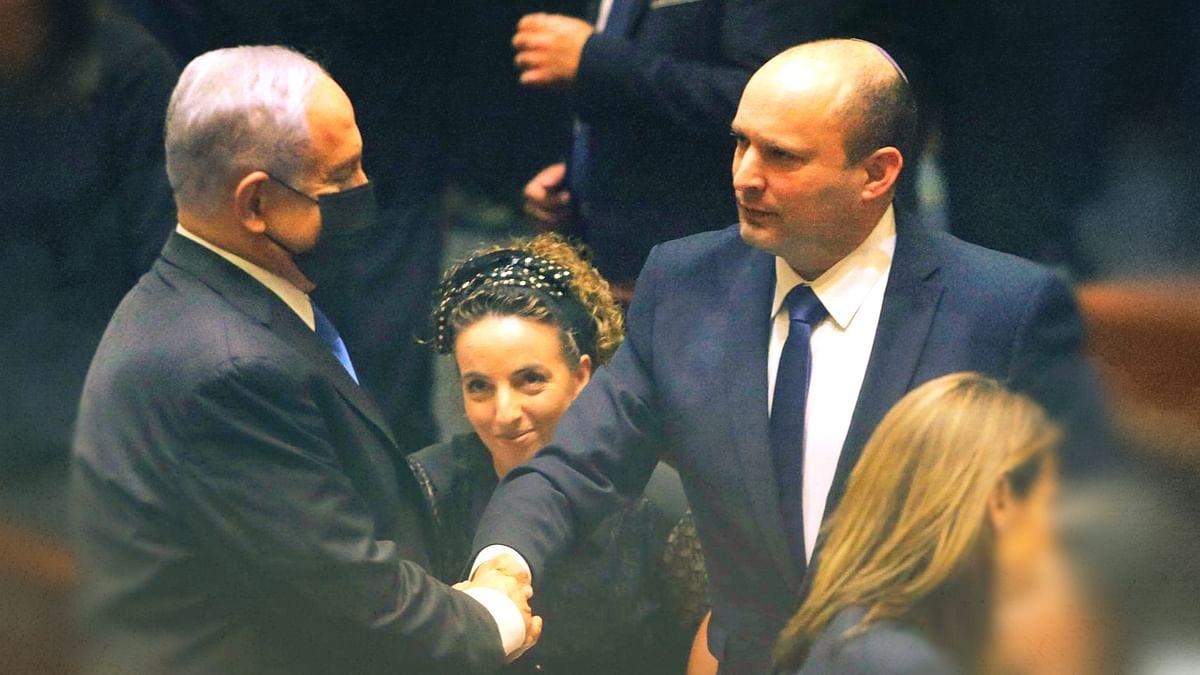 Israel's new Prime Minister Naftali Bennett greets Benjamin Netanyahu.