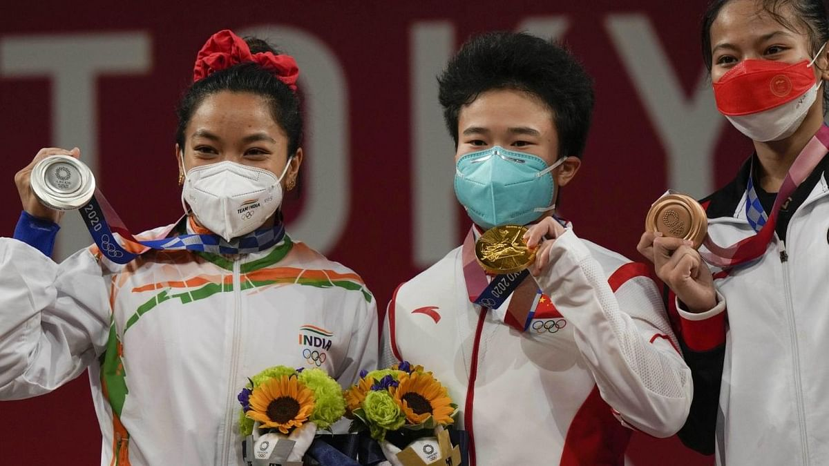 """<div class=""""paragraphs""""><p>Tokyo Olympics: Mirabai Chanu (extreme left) won Silver in the 49 kg event.</p></div>"""