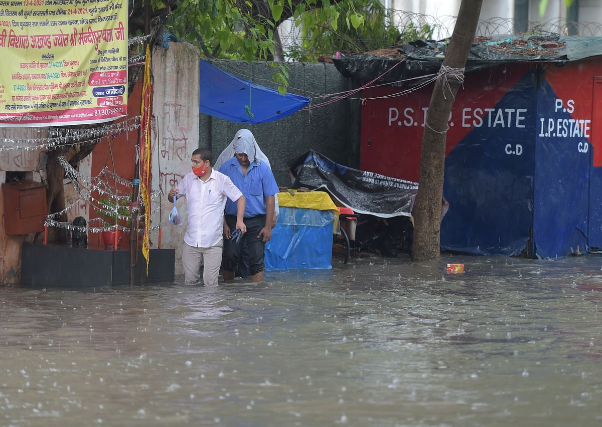 """<div class=""""paragraphs""""><p>People attempt to cross a waterlogged street during heavy rains.</p></div>"""