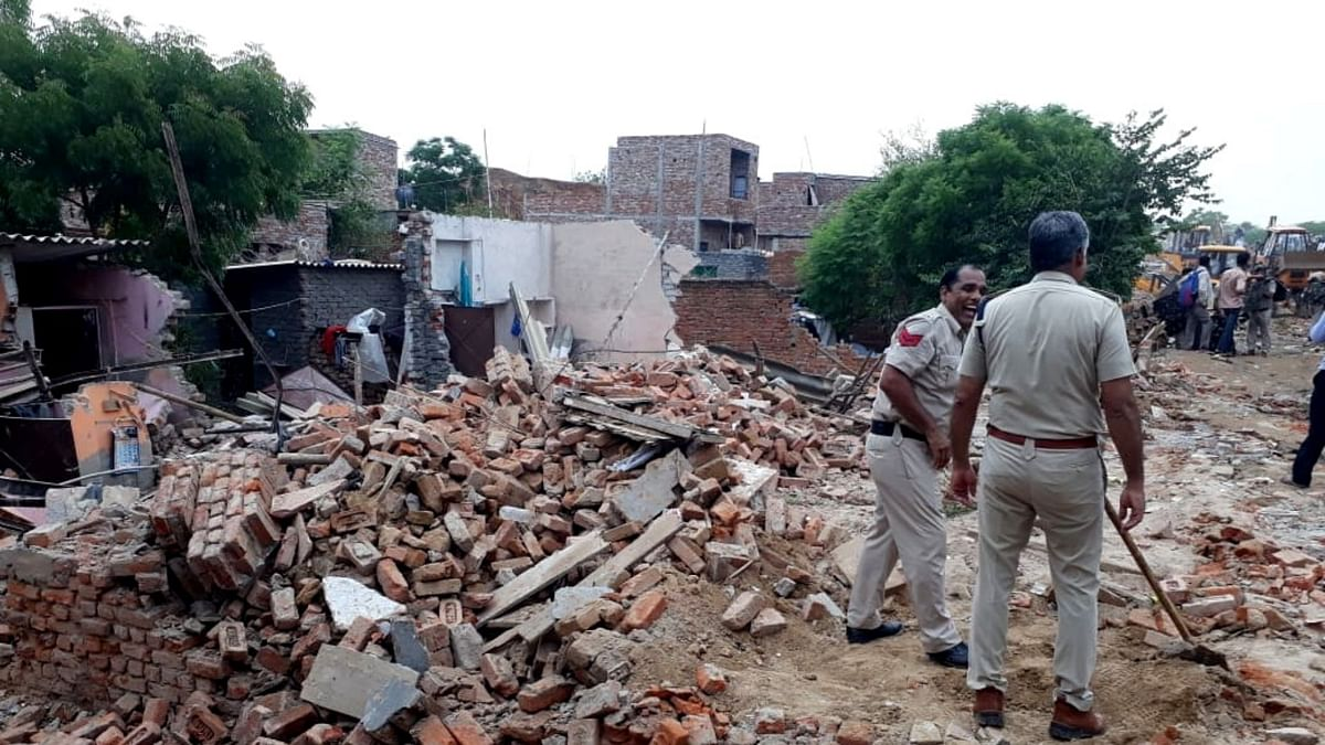 """<div class=""""paragraphs""""><p>As houses in the Khori Village are razed to the ground, Faridabad Police officials look on.</p></div>"""