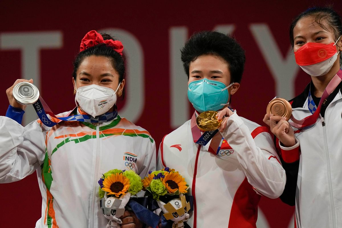 """<div class=""""paragraphs""""><p>Silver medalist India's Mirabai Chanu(L) with Gold medalist China's Hou Zhihui (M) and bronze medal winner AISAH Windy Cantika poses for photographs during the presentation ceremony of women's 49 kg category weightlifting event at the Summer Olympics 2020, in Tokyo, Saturday, July 24, 2021.</p></div>"""