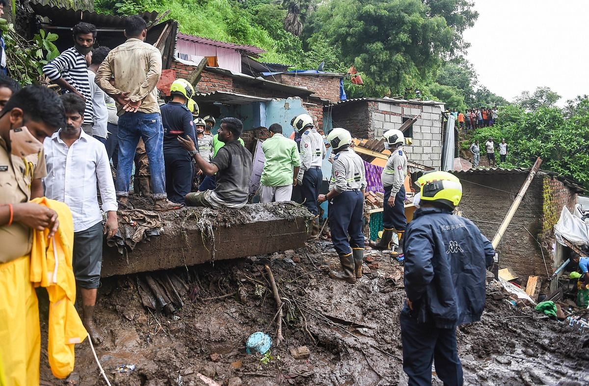 """<div class=""""paragraphs""""><p>Firemen and rescue workers after a wall collapsed on some shanties in Chembur's Bharat Nagar area due to a landslide, in Mumbai, on Sunday, 18 July.<br><br></p></div>"""
