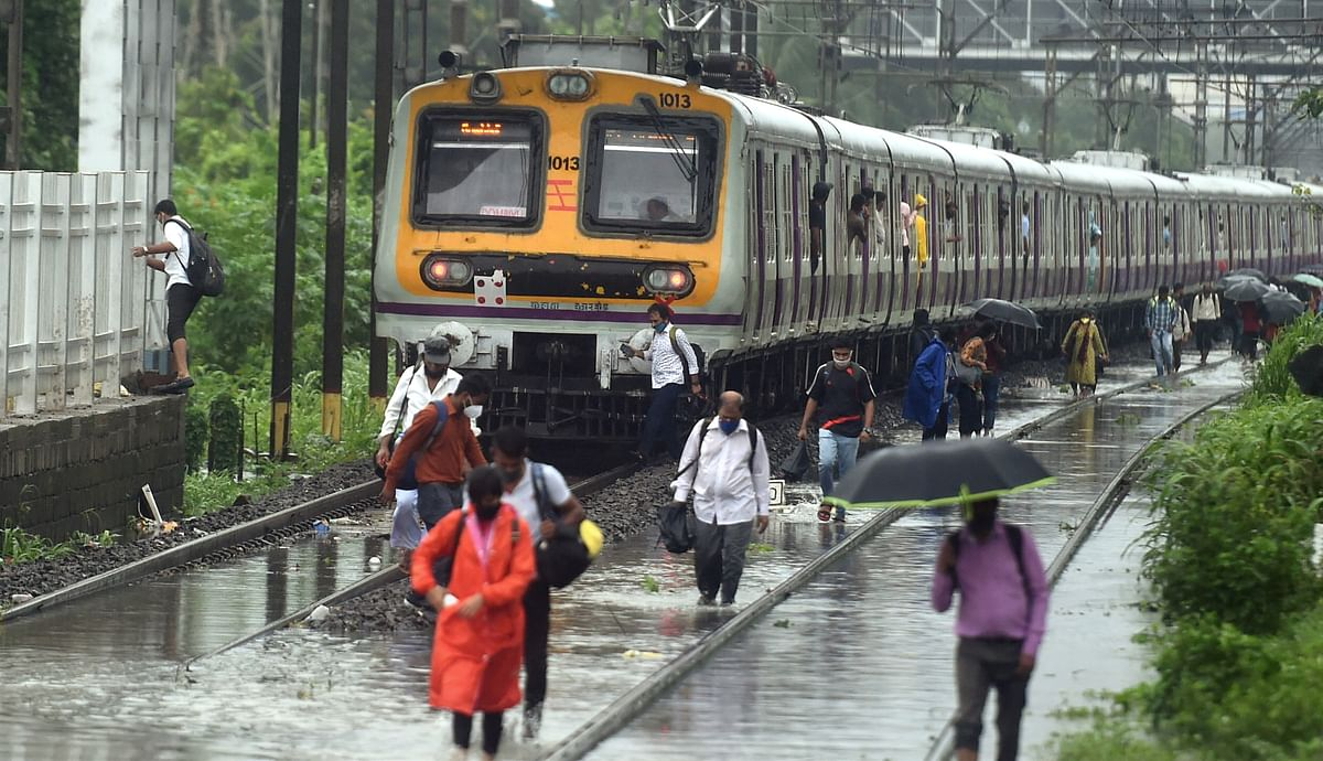 """<div class=""""paragraphs""""><p>Mumbai: People walk on the waterlogged railway tracks after local trains services were affected due to heavy rain, at Sion in Mumbai<br></p><p></p></div>"""