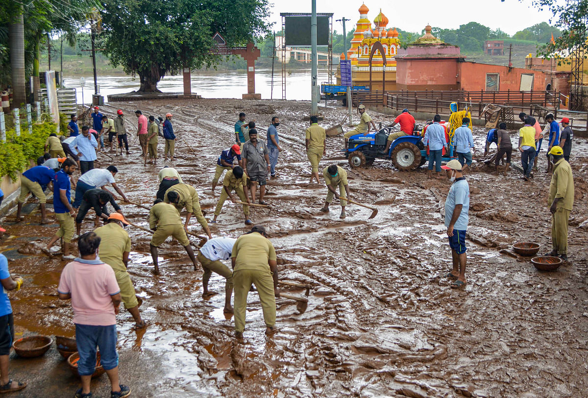 """<div class=""""paragraphs""""><p>Municipal workers remove mud after the recession of flood-water at Krishnamai Ghat in Karad, Monday, 26 July.</p></div>"""