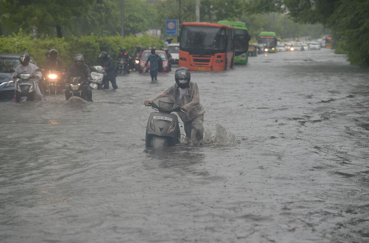 """<div class=""""paragraphs""""><p>A commuter pushes his scooter through a waterlogged street due to heavy rains, near ITO in New Delhi on Monday.</p></div>"""