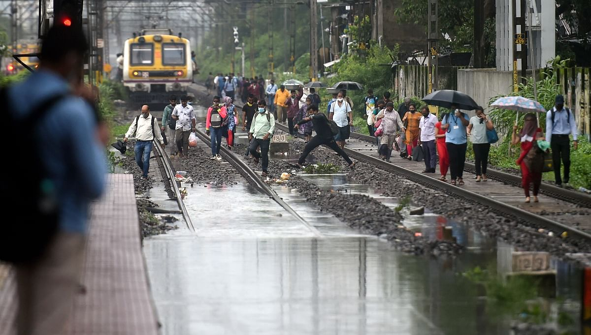 """<div class=""""paragraphs""""><p>Mumbai: People walk on railway tracks after local train services were affected due to waterlogging after heavy rains, at Sion in Mumbai<br></p></div><div class=""""paragraphs""""><p><br></p></div>"""