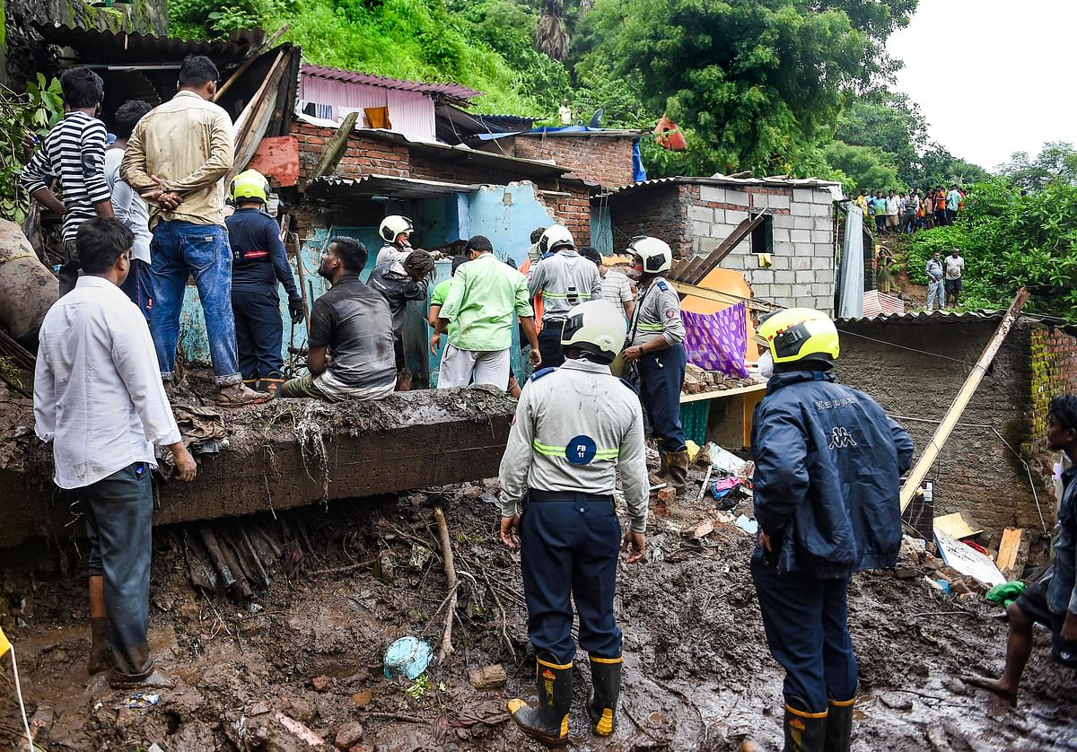 """<div class=""""paragraphs""""><p>Firemen and rescue workers after a wall collapsed on some shanties in Chemburs Bharat Nagar area due to a landslide, in Mumbai, Sunday, 18 July.</p></div>"""