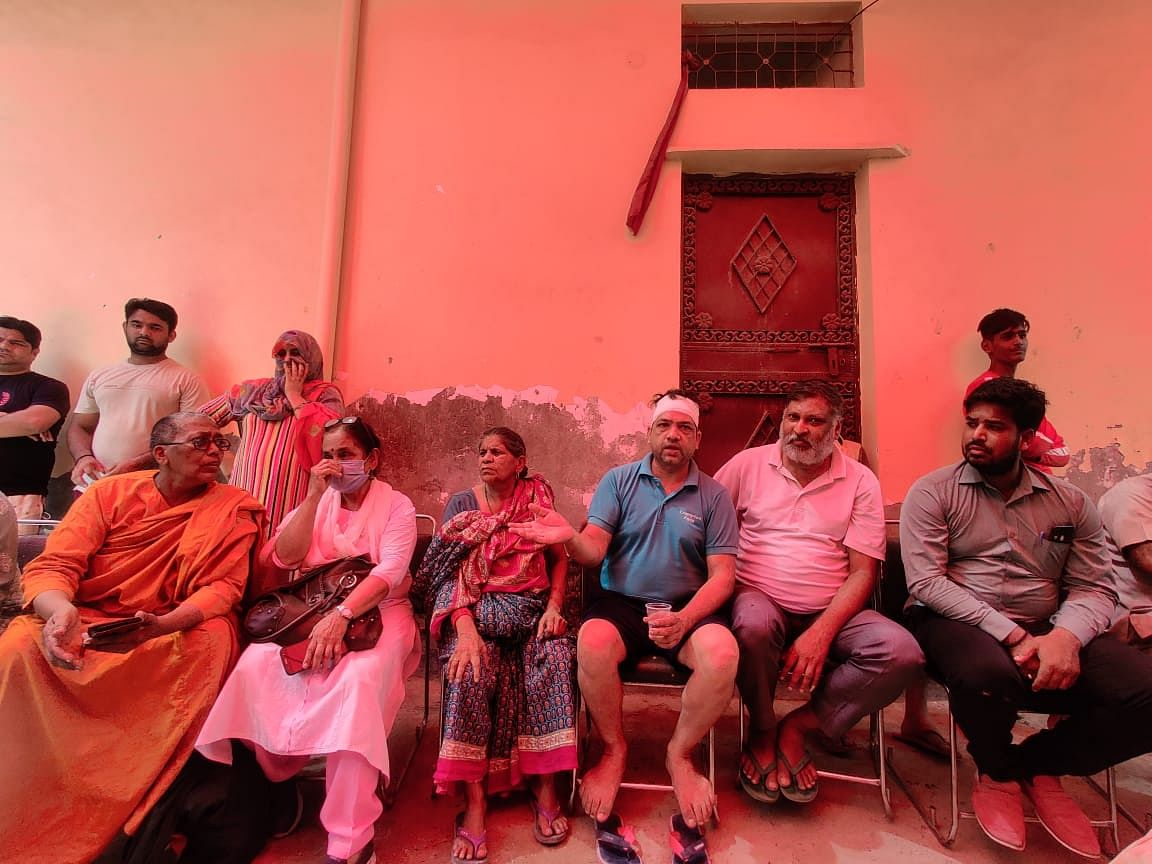 """<div class=""""paragraphs""""><p>Sitting in the middle (in blue), with a bandage on his head, is Ravi.</p></div>"""