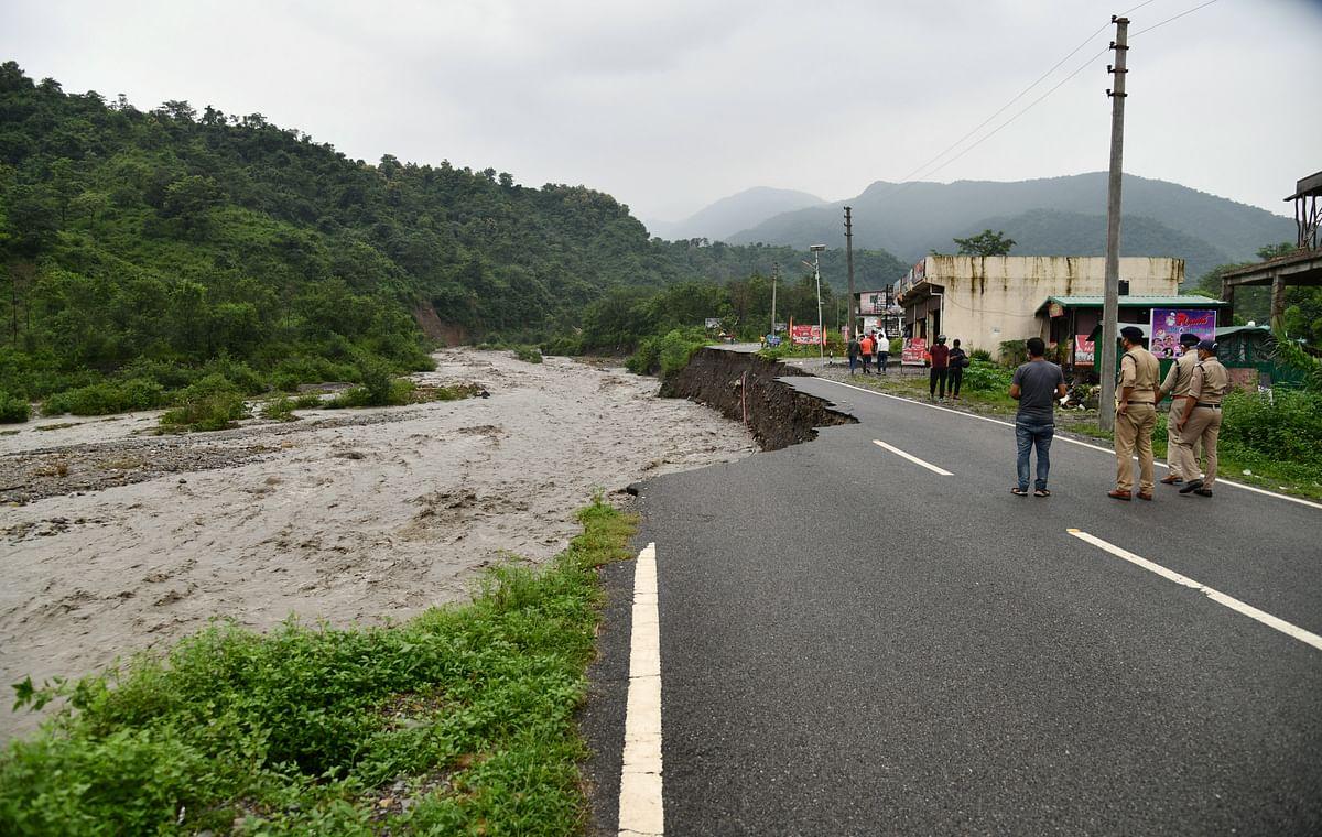 "<div class=""paragraphs""><p>Dehradun: Police personnel stand near the damaged part of the Sahastradhara-Raipur road, following heavy rains, in Dehradun, Friday,27&nbsp;August 2021.</p></div>"