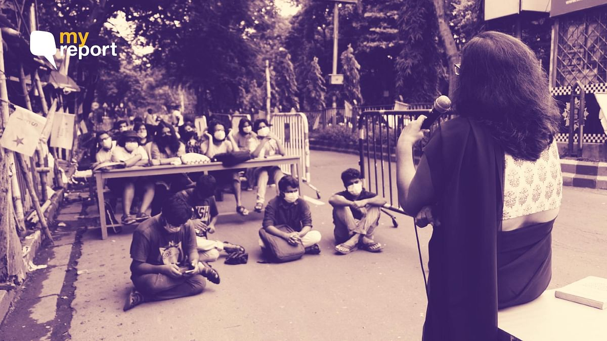 """<div class=""""paragraphs""""><p>Despite the rain, several students are turning up for these open-air classes on the pavement in front of Jadavpur University's gate.</p></div>"""