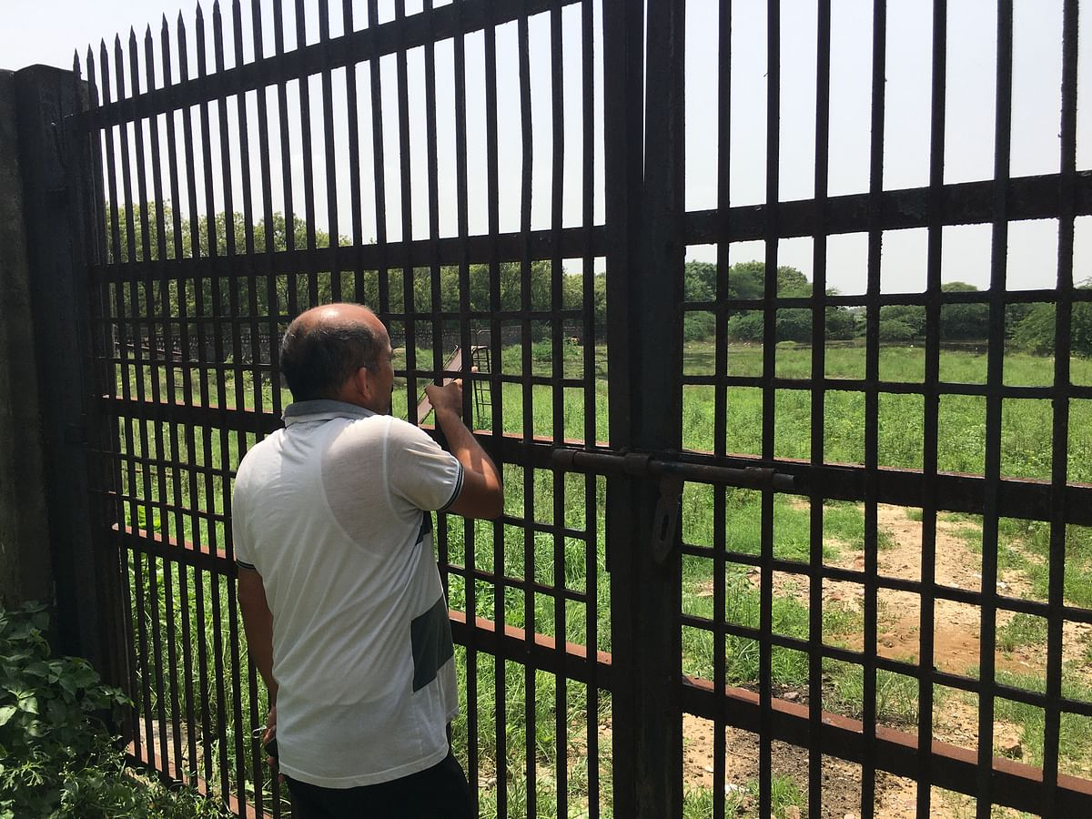 "<div class=""paragraphs""><p>Pavan Tyagi pointing towards the Jhatikara hospital boundary wall.&nbsp;</p></div>"