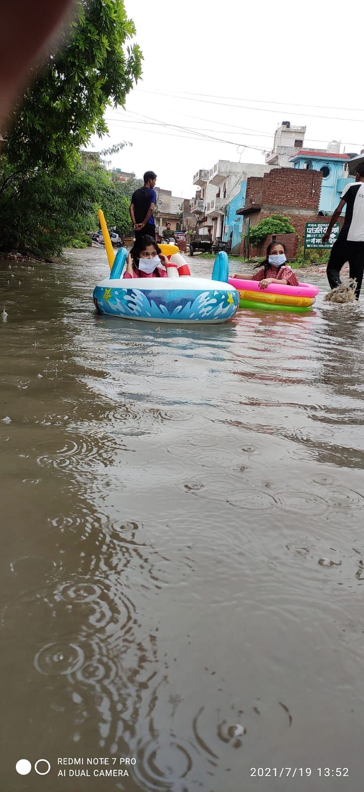 """<div class=""""paragraphs""""><p>Residents use an inflatable boat on the road amid heavy rain. Photo from 19 July.&nbsp;</p></div>"""