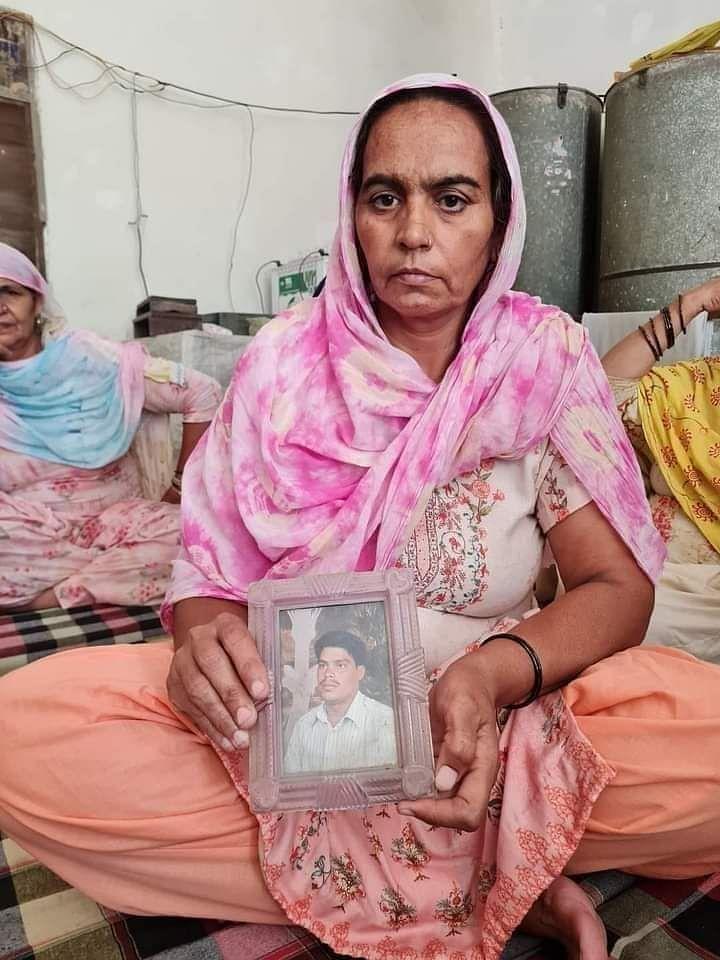 """<div class=""""paragraphs""""><p>Sushil's wife Sudesh Devi Kajal holds his picture after his death.</p></div>"""